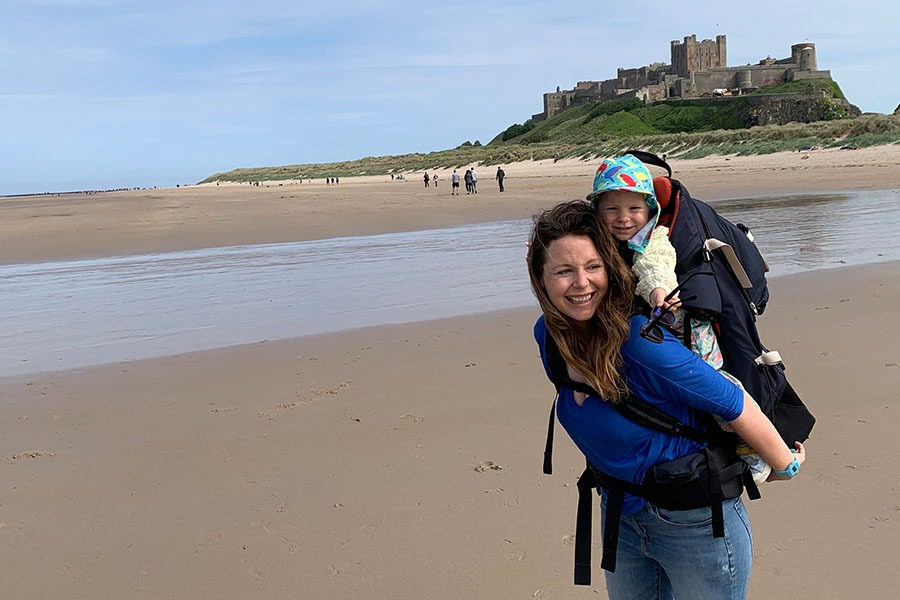 Mum and toddler on the beach by Bamburgh Castle