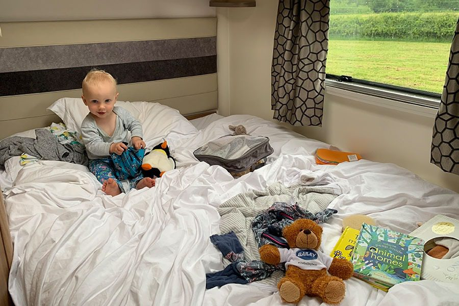 Toddler playing with toys on motorhome bed