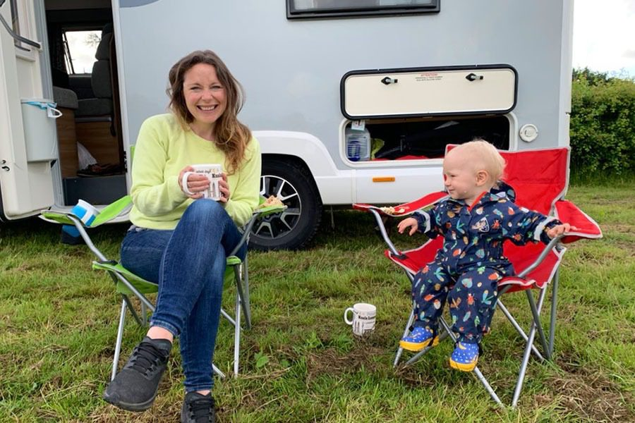 Mum and toddler sitting outside motorhome